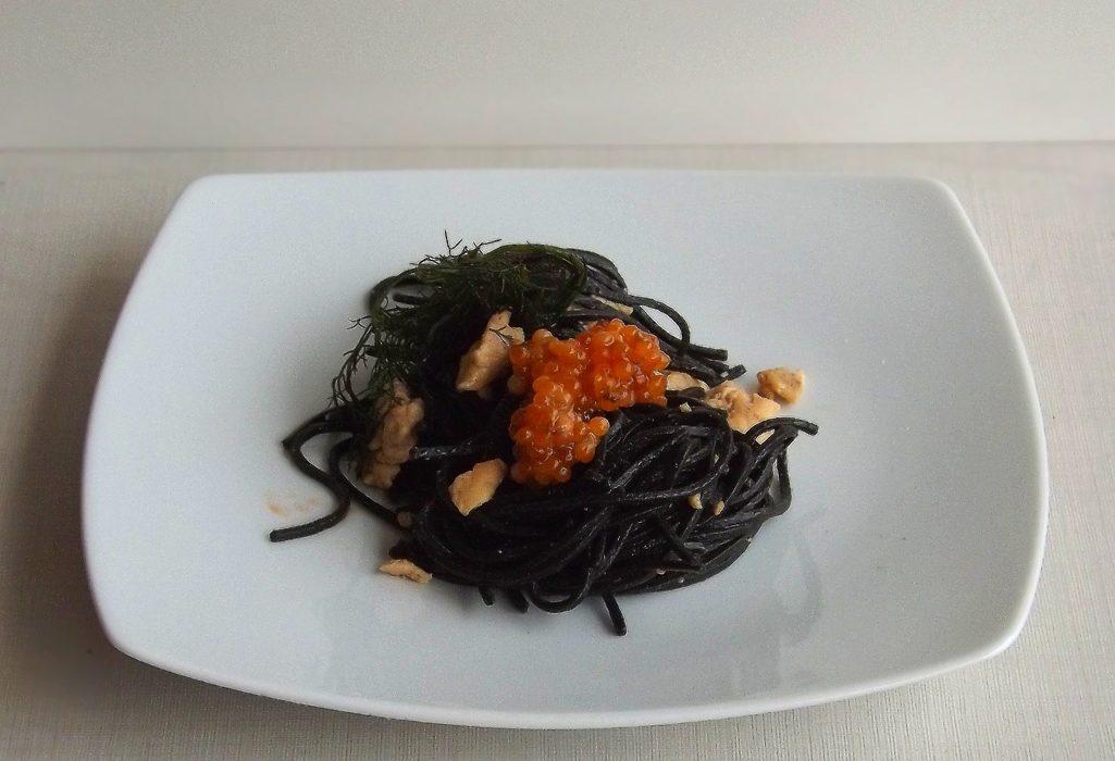 Spaghetti al nero di seppia con trota salmonata, mandorle e uova di trota