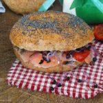 Bagel farcito con salmone, feta, pomodori confit e germogli