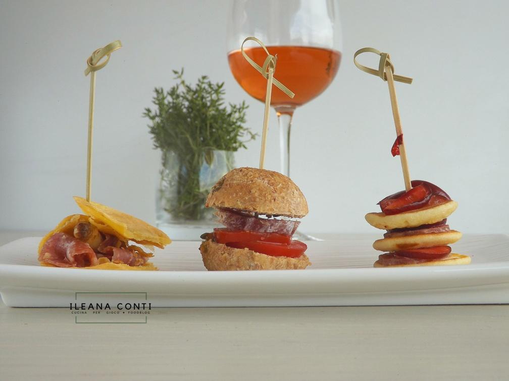 I tre morsi, aperitivi mignon a base di salumi clai: Minipanino salame e pomodoro; farinata con asparago bianco e salame; minipancake con ciliegia e salsiccia